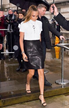 CARA DELEVINGNE The Brit beauty didn't like the weather rain on her style—she stepped out in a white tee, leather skirt, a statement necklace, and black sandals.