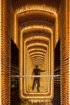 """Matadero Cineteca"" in Madrid (film library and movie theater) designed by the spanish architects CH+QS...The space glows with dozen of golden Led tubes making the library looking like a futuristic spaceship."
