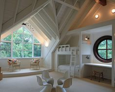 Whimsical attic room with exposed framing, built in bunks and awesome round window!