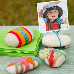 R Is For Rocks. Stay Put: Wrap colorful yarn around a palm-size stone to use as a napkin, balloon, or blanket weight when partying outside. Stand Tall: Use easy-to-bend wire to make a photo holder for your child's first birthday party. Glue pebbles to the bottom of the larger rock to make it level. Buy wire at JamaliGarden.com.