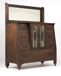 English Arts and Crafts Oak Sideboard. Early 20th century, the rectangular backsplash inset with a beveled mirror plate, over a breakfronted top above a pair of cupboard doors inset with clear, frosted and green slag glass panels, flanked on either side by three short drawers, over a long drawer, mounted with patinated metal hardware, on bracket feet raised on casters.