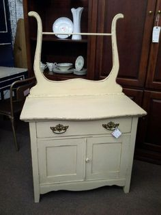 """$199 - This antique oak washstand has 1 double door cabinet and a single Knapp joint constructed divided drawer for storage. Original hardware and towel harp. It has been painted a rich cream, distressed and finished in a had applied tinted wax. It measures approximately 33 inches across the front by 19 inches deep and stands 29 to top surface and 54"""" at tallest point.  It can be seen in booth D 17 at Main Street Antique Mall 7260 East Main Street ( E of Power Rd ) Mesa, AZ 852..."""