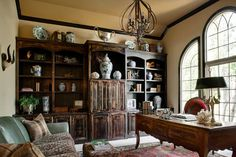 Rustic home office with distressed bookshelf, wooden desk, black crown molding, chandelier, blue and white porcelain