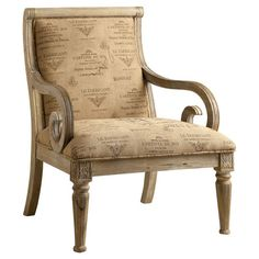 Scrolling fluted arms and carved details highlight this wood-framed arm chair, featuring French typographic upholstery and a white wash finish.
