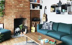 Stue med grønn sofa og en ubehandlet murvegg.