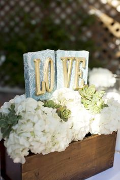 The low centerpieces will be distressed, white, wooden boxes overflowing with lush white hydrangeas and green succulents surrounded by tall and short votives.  (No LOVE sign).  : )