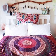 Pink purple and coral ikat tribal bedding in neutral room. Natural wood branch headboard art.
