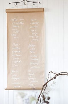WALL DECOR :: A simple scroll of brown paper w/ white writing hung from a wire hanger. Cute.