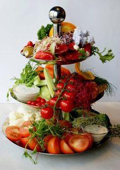 De Saladetuin: Etagiére met diverse rauwkost & dip en vegetarische tapas   Drie-laags etagiére voor ca. 16 personen voor op tafel. Gezond en smakelijk!  Bevat: Selderie-bites wortel-bites Paprika-bites Broccolli & Bloemkool-bites Tomaatpartjes Yoghurt dipsaus Gevulde pepers met roomkaas Gevulde olijfmix