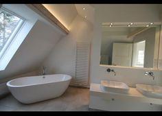 Traumhaftes, helles Badezimmer im Dach mit frei stehender Badewanne und Doppelwaschtisch.