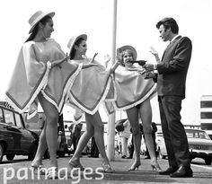 """A posse of pretty girls in ponchos are invited to 'reach for the skies' by Clint Eastwood, 6ft 4in star of the new western """"A Fistful of Dollars"""". As 'the man with no name' Clint has three trademarks in the film -- poncho, short cigar and long gun. 1st June 1967"""