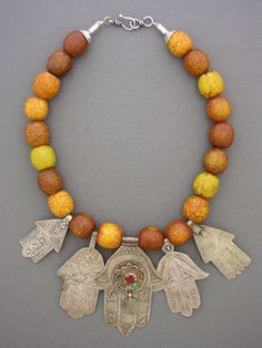 """Five antique hamsas from various parts of Morocco sit beneath a strand of crackled """"African amber"""" bakelite beads from Africa. The Hamsa hand is a traditional amulet used to ward off the jealous or evil eye, and has been used throughout the Middle East for centuries. Sterling silver cones and hook and eye clasp."""