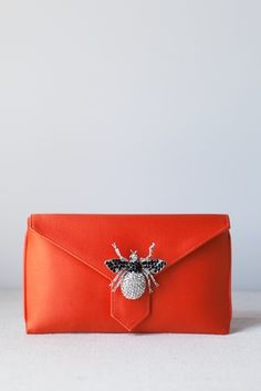 India Hicks. orange clutch with bug detail.