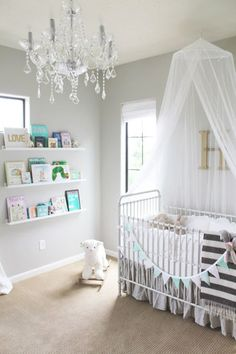 pale grey walls, striped blanket, pastel bunting, lamb toy, chandelier