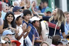 Paulina Gretzky high fives fans after Dustin Johnson hits his approach shot on the 18th green before making a birdie on the first playoff…