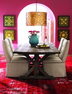 crazy colorful dining room! love the farmhouse table, upholstered chairs, bright pink wall with contrasting gold drum shade chandelier