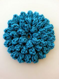 There are a plethora of crochet flower patterns out there but this one is truly unique. With a single round, it makes a perfect accent for a headband or hat, with two rounds it can be used to make a beautiful motif or if you keep crocheting you can make a large round accent pillow. This beautiful flower works up quick and easy and has wonderful texture.