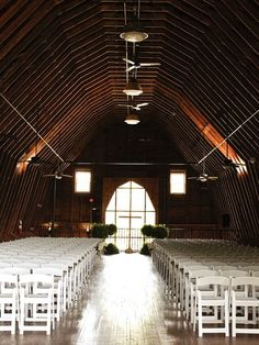 White chairs lined up for a barn wedding.