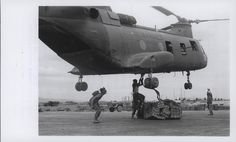 "CH-46 Helicopter Delivers Supplies, 1969 ""Marine Catering Service: A Marine CH-46 helicopter hovers over the Landing Zone at An Hoa Combat Base, south of Da Nang, as Force Logistic Command Leathernecks rig a combat sling filled with supplies for Marines participating in Operation Taylor Common. This helicopter 'catering service' is the only way that many Marines participating in the operation can be resupplied (official USMC photo by Lance Corporal John Volpe)."" From the Jonathan Abel…"