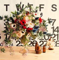 Cherry-red ranunculi, anemones, garden-fresh jasmine, scabiosa pods, spray roses, and blue thistle | Design Sponge