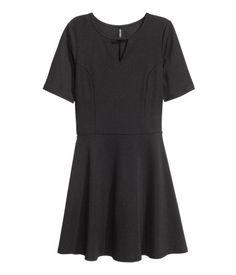 Musta. Lyhyt mekko ribattua trikoota. Halkio pääntiessä, vyötäröleikkaus ja väljä hameosa.