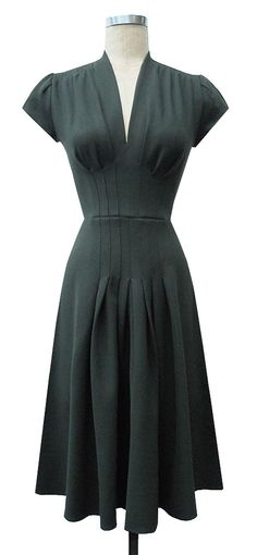 V-neckline and classic darted short sleeves. The darts extend from under the bust to the fullness of the hips . There is gathering at the top of the shoulder and the skirt has a kicky wide a-line shape. The back is simple and fitted with only a waist seam.  Jenny Short Sleeve Dress | Trashy Diva