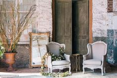 This pair of tan linen chairs Dakota & Shiloh are stunning.  Perfect for lounge spaces or bride and groom chairs. Lovely garland by Gertie Mae's Floral design. #event-rentals,#furniture-rentals,#lounge-furniture-rentals