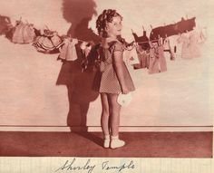 1935 Shirley Temple with a clothesline full of Ideal Shirley Temple doll's clothes
