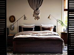 Ein Schlafzimmer mit BRUSALI Bettgestell in Braun, LINBLOMMA Bettwäsche-Sets in Naturfarben, BRUSALI Ablagetisch in Braun und vernickelten BAROMETER Stand-/Leseleuchten