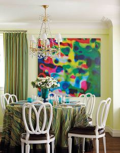 """Curtains in the dining area are in Drake's Jazzed for Schumacher, a cotton whose stripes alternate between matte and sateen, """"giving a sense of depth and movement,"""" he says. """" I had fun bringing my Blades fabric from the sofa pillows to the dining table. It provides cohesiveness."""" The painting is by Irene Mamiye. """"To some, this piece might seem to clash, but when art gets too matchy-matchy with the decor, it loses its edge."""" Chairs from Artistic Frame have seats in Larsen patent leather…"""