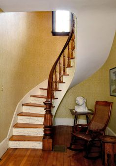 Curved staircase with original wood railings in foyer of 1860s farmhouse.