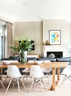 Dining room with large wooden table, white and metal chairs, clear vases with greenery, and abstract art over the fireplace mantel.