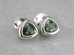 Utterly simple, these lovely earrings are crafted of fine 14k white gold, trillion cut deep green glittering tourmalines are securely bezel set and ready to wear day or night! Metal: 14K White Gold Gem: 2 Green Tourmaline Gem Measurements: 5 mm, Trillion Earrings Length: 8 mm Earrings