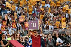 TOPSHOT - Roma's forward from Italy Francesco Totti holds a framed Number 10 during a ceremony to celebrate his last match with AS Roma after the Italian Serie A football match AS Roma vs Genoa on May 28, 2017 at the Olympic Stadium in Rome. Italian football icon Francesco Totti retired from Serie A after 25 seasons with Roma, in the process joining a select group of 'one-club' players. / AFP PHOTO / Vincenzo PINTO