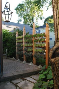 Top that neighbor! Get creative in the your yard, with hand carved wooden posts. Birds grace the supports on a vertical herb garden privacy fence. Deck and patio upgrade.