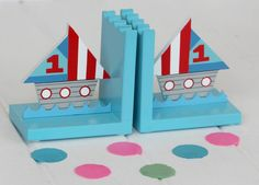 Wooden Ship Bookends  A lovely pair of handcrafted Ship Bookends, a great finishing touch to a child's bedroom or nursery. Brighten up your nursery or shelves with these lovely wooden bookends. These bookends feature a nautical theme and would be a perfect present for any child who loves the sea. Hand Painted with non-toxic paint, these gorgeous bookends are strong enough to keep books in place whilst adding a splash of fun to any child's space.