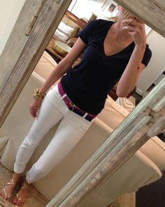 White pants with simple navy shirt tucked into pants, and set off by a colorful belt.