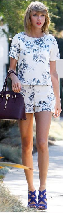 White floral shorts, blue rose print tee, red handbag, and purple suede sandals