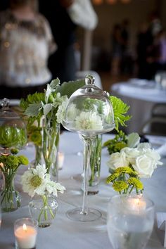 smaller vases with flowers, tea lights & then table theme on platform/candleholder in center
