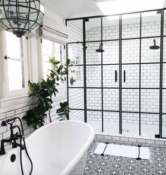 Bathroom with black hardware, black framed shower doors, black and white patterned encaustic tile floor - wow!
