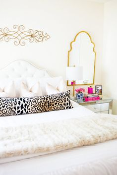 gal about town glam bedroom with white bedding and leopard pillows, gold mirror, and fur throw
