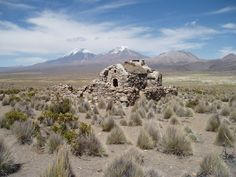 Deserted house at Sajama National Park, Bolivia with twin Chilean volcanoes Parinacota and Pomerape behind it.