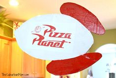 To make your own, download the Pizza Planet Logo. The rocket ship is cut out of cardboard, which I spray painted red and white. Then I glued the printed logo on the sign and used a layer of Mod Podge to seal my double-sided sign. (Yes, it is a double-sided sign.)