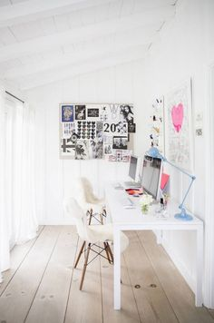 Feminine office space with pops of pastel colors,  and sheep throws over mod white chairs