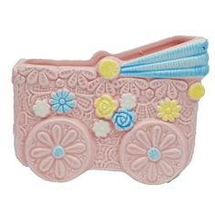 Vintage pre-owned collectible glazed porcelain ceramic flower planter from Inarco in the shape of a baby stroller or carriage. Pink figural baby carriage, stroller, buggy or pram with a pink floral decorated base and blue, yellow and white accents.  Originally used to hold floral arrangements, this could be re-purposed to hold various items in the baby nursery. #Inarco #Planter #EverythingsCollectible #CollectItAll