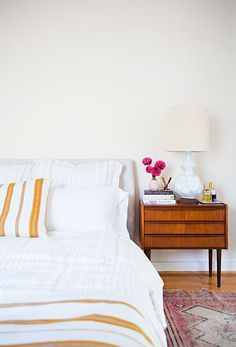 a subtle pop of color on an all white bedroom is inviting and peaceful.