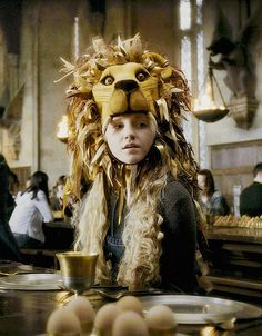 """Luna Lovegood had drifted over from the Ravenclaw table....She had managed to procure a hat shaped like a life-size lion's head, which was perched precariously on her head."""