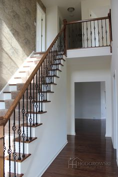 Make an entrance with beautiful wrought iron spindles on oak treads with faux brick wallpaper like this homeowner did in Travers Meadow.