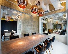 The office's meeting and conference rooms continue the themes set in the adjoining reception area, with their wood veneered tables and copper fixtures contrasting against the industrial flavour of brick walls, exposed ceilings, and a white epoxy floor