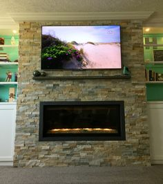 Beautiful Family Room Fireplace, Lowe's Desert Quartz ledge stone, contemporary modern fireplace, custom white built in cabinets and glass shelves, grays, browns, TV.